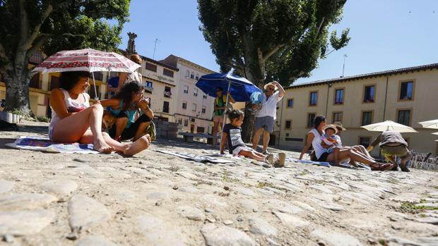 Varias personas con toallas y sombrillas protestan por la remodelación de la Plaza del Grano de León