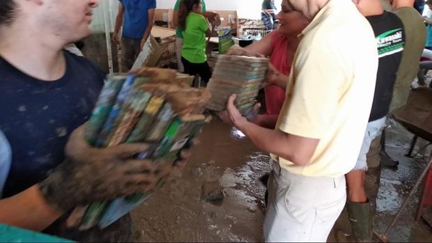 Trabajadores y vecinos recogiendo los libros llenos de barro este domingo
