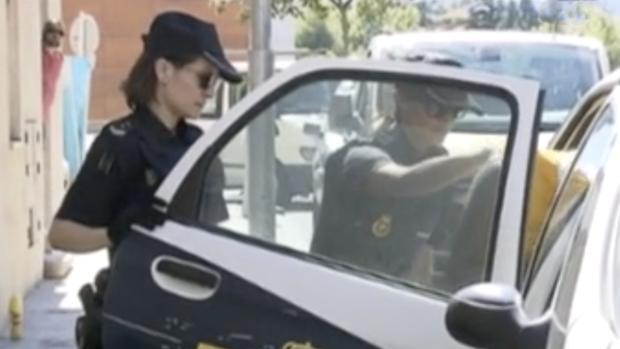 Momento en que dos agentes introducen al acusado en un coche patrulla para trasladarle a prisión