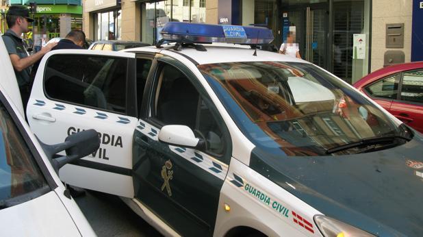 El detenido, custodiado por la Guardia Civil junto a la entidad bancaria donde ha sido identificado