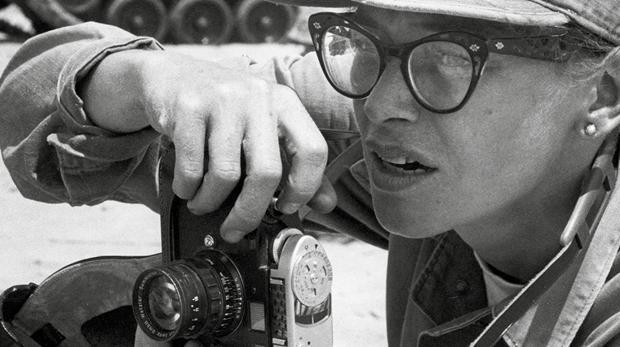 Imagen de una reportera, cámara fotográfica en mano, en una zona de conflicto