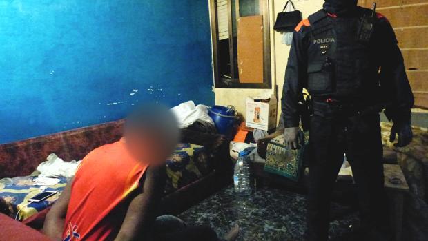 Un agente de los Mossos con uno de los detenidos