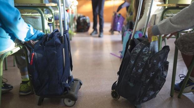 Dos escolares con sus mochilas cargadas de libros de texto