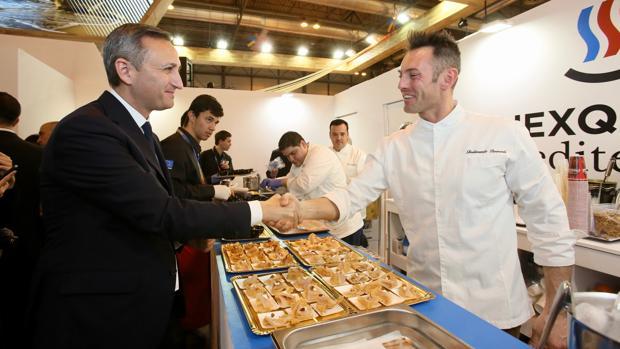 César Sánchez saluda a un cocinero en la feria de turismo de Madrid