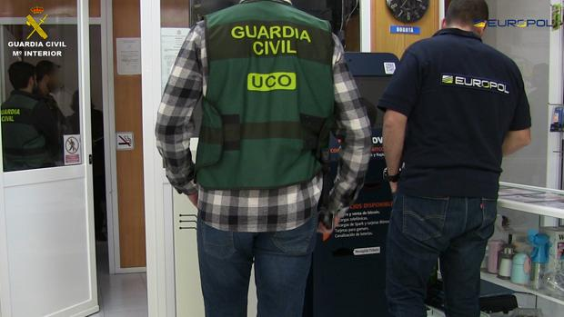 Agentes de la UCO de la Guardia Civil y de Europol, ante un cajero de bitcoins intervenido en una de las empresas que formaban parte de esta red de blanqueo