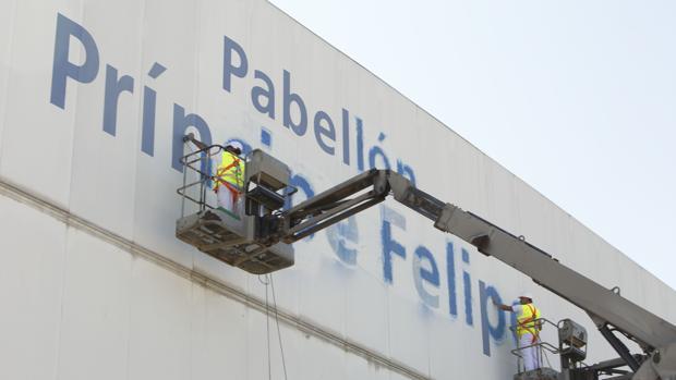 Operarios borrando el nombre del pabellón por orden del gobierno municipal, hace cuatro años