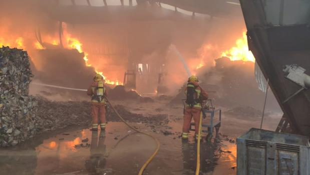 Efectivos de bomberos trabajan en la extinción del incendio en la plata de reciclaje