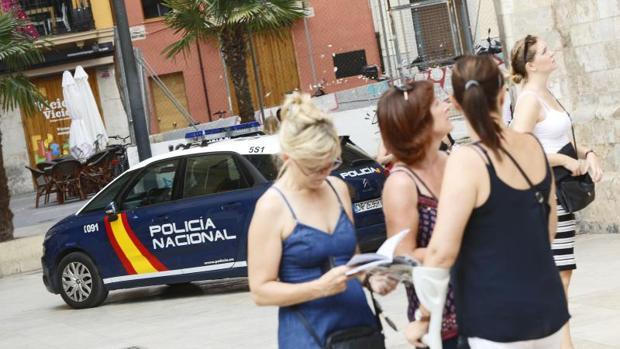 Varias mujeres junto a un coche de la Policía Nacional en Valencia