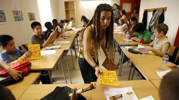 Una profesora reparte material a los alumnos en una escueka de Vic