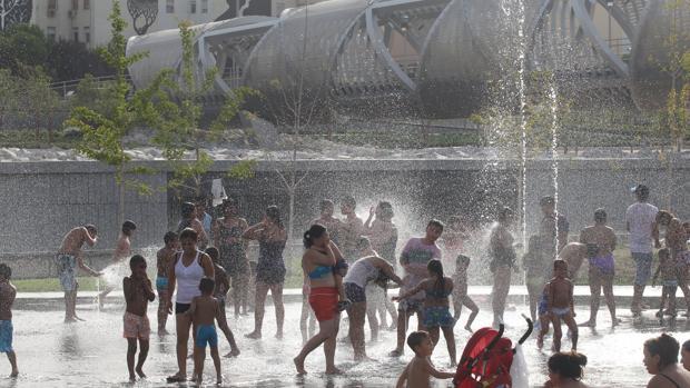 Un grupo de gente se refresa en las fuentes de Madrid Río por la ola de calor
