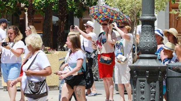 Imagen de archivo de unos turistas en Valencia protegiéndose del sol