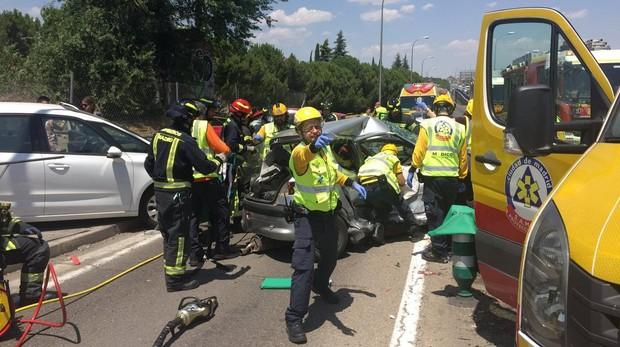 Bomberos y sanitarios atendiendo a los heridos en el lugar del accidente