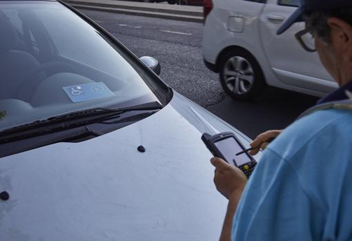 Un operario del SER apunta en su dispositivo el número de una autorización para minusválidos