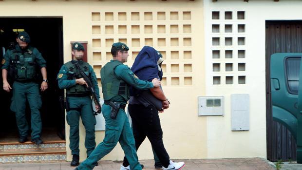 Agentes de la Guardia Civil trasladan a un detenido durante uno de los registros realizados en una vivienda de la calle Espartel en la barriada del rinconcillo en Algeciras (Cádiz)