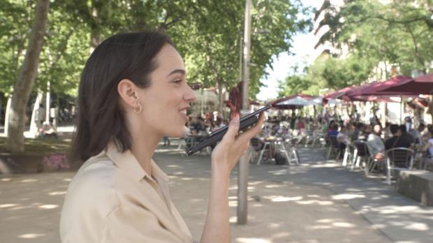 """Una joven, con una batería para cargar el """"smartphone"""""""