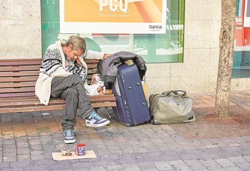 Un hombre sin hogar duerme en un banco de la avenida de la Libertad, junto a sus enseres