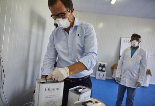 Pedro Laguna envasando latas de su aceite ecológico en su almazara de Villaconejos