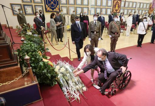 The minister helps lay flowers to one of the relatives of the deceased