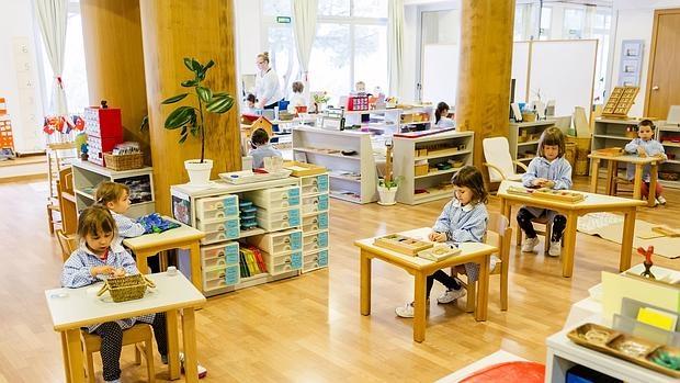 Aula Monessori con niños trabajando y guía al fondo