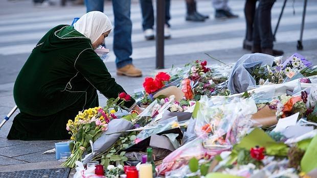 Una mujer deja una flor en recuerdo de las víctimas de los atentados