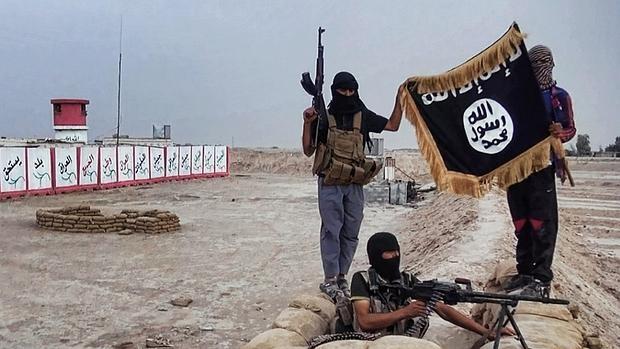 Combatientes de Daesh muestran una bandera de la organización terrorista