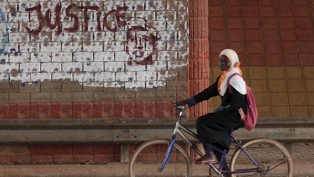 Una niña pasa junto a un grafiti que pide «justicia» junto a un retrato del asesinado expresidente Thomas Sankara en Uagadugú, Burkina Faso