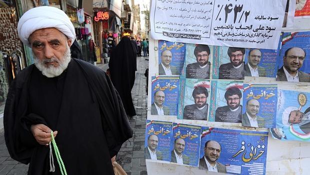 Un clérigo pasa ante un cartel electoral en la ciudad iraní de Qom