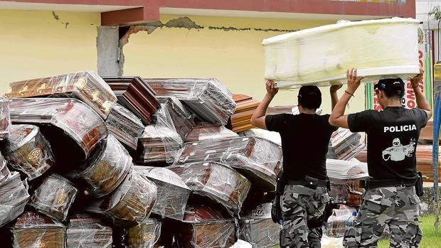 Dos policías apilan ataúdes para algunas de las 499 víctimas del seísmo, según la última cifra ofrecida por el Gobierno