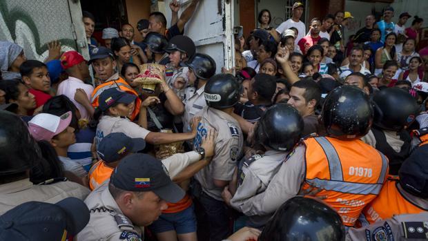 La Policía Nacional Bolivariana contiene a un grupo de personas que trata de entrar en un supermercado donde venden dos kilos de pasta por persona, este viernes en El Valle (Caracas)