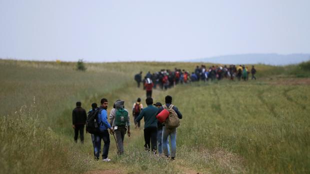 Un grupo de refugiados salen del campo de Idomeni para cruzar la fronter que separa a Grecia de Macedonia