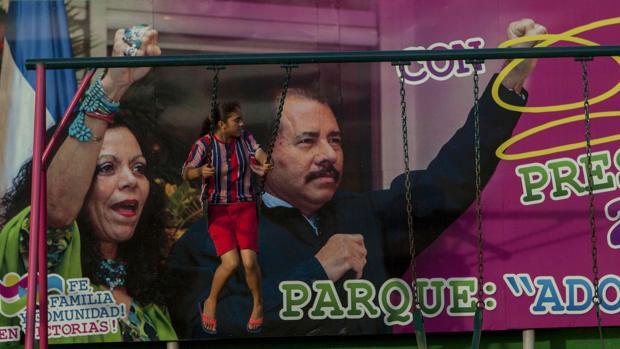 Una niña juega frente al cartel electoral a favor del candidato a la reeleción Daniel Ortega, y la aspirante a vicepresidenta, Rosario Murillo
