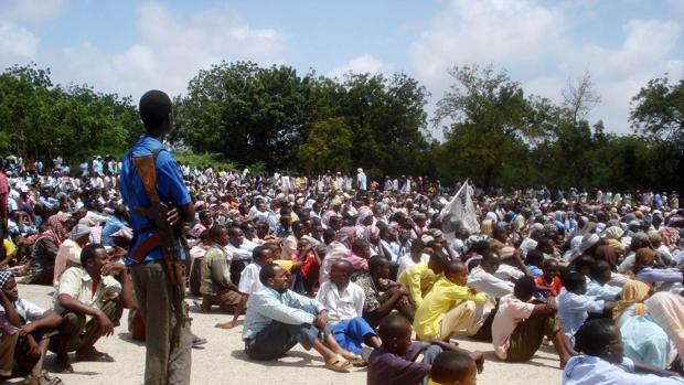 Un soldado armado de Al Shabab vigila a una gran audiencia de somalíes en la capital, Mogadiscio