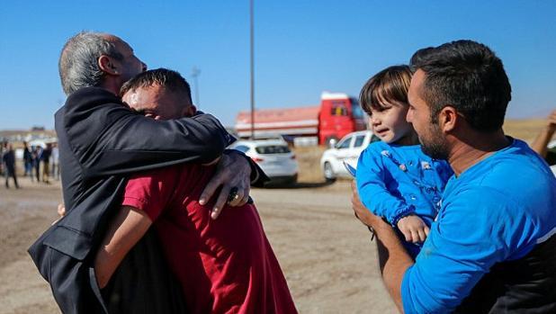 Un padre abraza a su hijo tras reencontrarse después de varios años sin verse