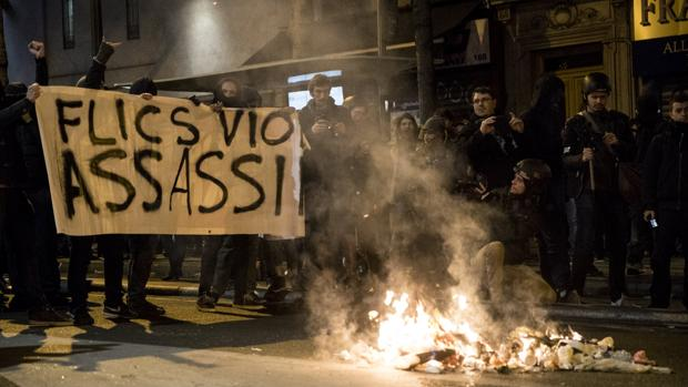 Varias personas sostienen una pancarta en la que se puede leer «Policías, violadores, asesinos» durante una manifestación en solidaridad con Théo y contra la violencia policial en París