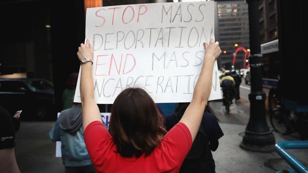 Una manifestante marcha por la calles de Chicago con una pancarta en la que pide por el fin de las deportaciones masivas