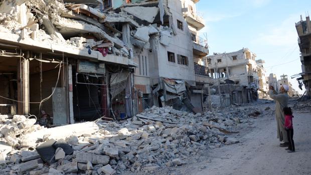 Un hombre toma fotos de las casas destruidas en Al Bab