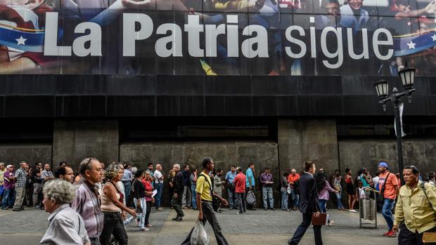 Una larga cola de venezolanos espera para poder retirar dinero de un cajero
