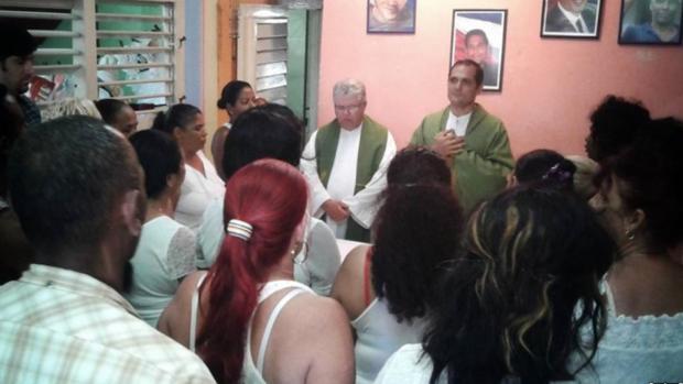 Los padres cubanos José Conrado y Castor Álvarez (d), oficiando una misa en la sede de las Damas de Blanco
