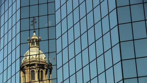 Vista de una de la cúpulas de la catedral de Santiago reflejada en un edificio