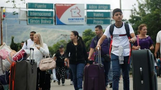 Un joven venezolano empuja su equipaje, mientras cruza el puente Simón Bolivar para llegar a Colombia