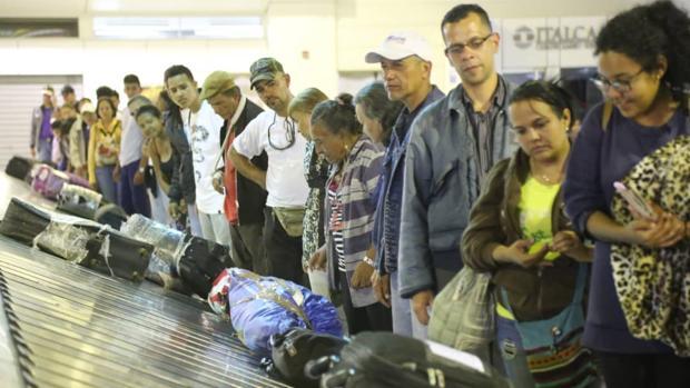Venezolanos esperan su equipaje en el aeropuerto de Caracas