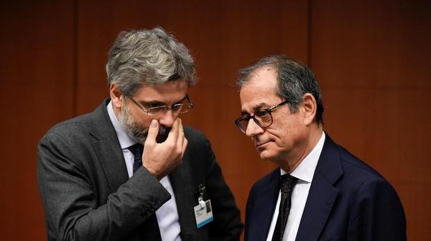 Un asesor habla con el ministro italiano de Economía, Tria, en la reunión de ayer en Bruselas