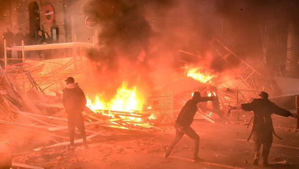 Manifestantes lanzan proyectiles frente a una barricada en llamas