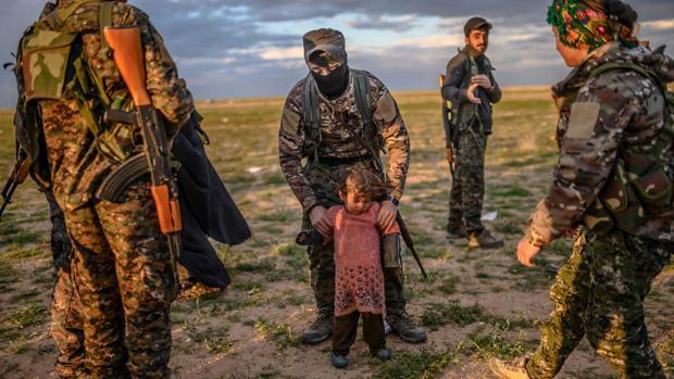 Soldados kurdos que cercan Baghouz con una niña que forma parte de los civiles evacuados