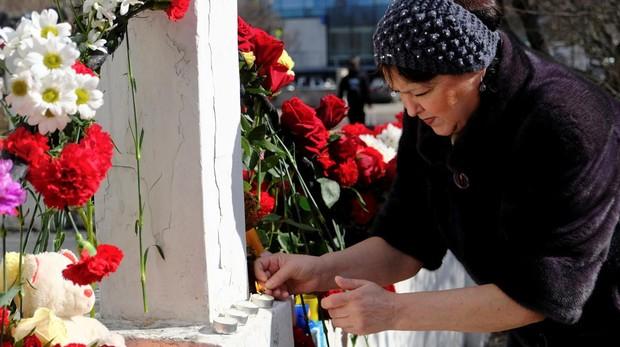 Una mujer pone flores en memoria de las víctimas del accidente del avión