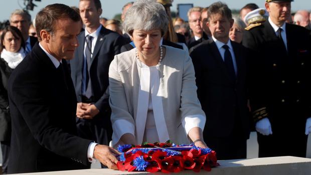 Emmanuel Macron y Theresa May realizan una ofrenda floral durante la colocación de la primera piedra de un monumento británico