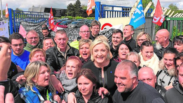 Le Pen con trabajadores de una fábrica en Amiens, en abril de 2017