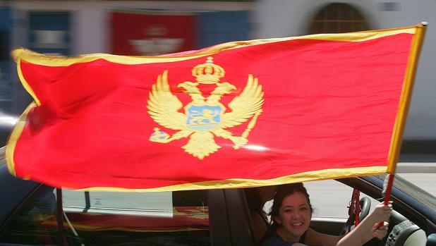 Una mujer sostiene la bandera de Montenegro tras la victoria del bloque independista en 2006