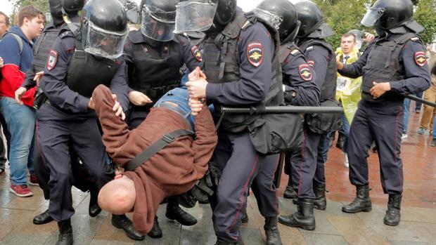 Varios policías antidisturbios se llevan en volandas a un manifestante durante una protesta opositora en el centro de Moscú