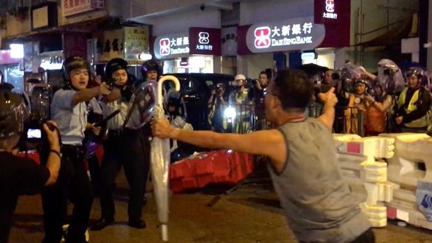 Un vecino se interpone entre la Policía y los jóvenes manifestantes, que atacaron a varios agentes que sacaron sus armas para defenderse